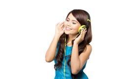 Młoda kobieta słucha muzyka z hełmofonem, odizolowywającym zdjęcie stock