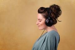 Młoda kobieta słucha muzyka z kopii przestrzenią z hełmofonami zdjęcie stock