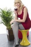 Młoda Kobieta Siedząca na stolec Iść na piechotę Krzyżuje Cieszący się szkło czerwone wino fotografia royalty free