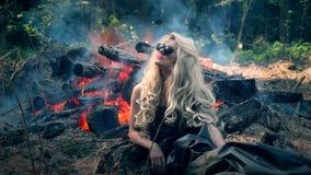 Młoda kobieta siedzi blisko jaskrawych spojrzeń i ogniska wokoło zbiory wideo