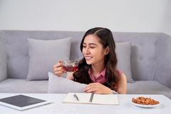 Młoda kobieta siedzi blisko leżanki w domu i pije kawę zdjęcia royalty free