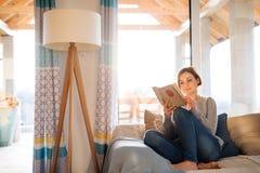 Młoda kobieta siedzi indoors na kanapie w domu, czytający książkę zdjęcia stock