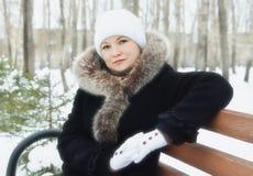 Młoda kobieta siedzi na ławce w zima parku Zdjęcie Royalty Free