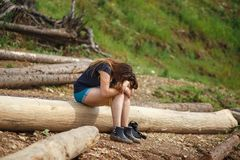 Młoda kobieta siedzi na spadać drzewie Wieszał głowę Pojęcie zmęczenie fotografia stock