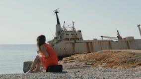 Młoda kobieta siedzi na torbie i cieszy się pięknego widok na morzu zbiory wideo