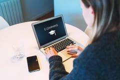 Młoda kobieta siedzi przy stołem i używa laptop z inskrypcją - nauczanie online, na ekranie zdjęcie stock