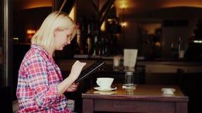 Młoda kobieta siedzi przy stołem w wygodnej kawiarni Używa pastylkę Miasto Graz w Austria zbiory