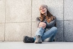 Młoda kobieta siedzi samotnie obok granit ściany Obrazy Stock