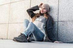 Młoda kobieta siedzi samotnie obok granit ściany Zdjęcie Royalty Free