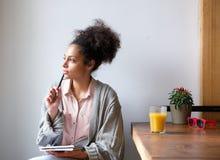 Młoda kobieta siedzi w domu z piórem i papierem Obrazy Stock