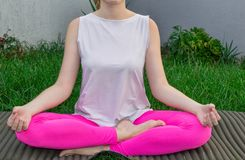 Młoda kobieta siedzi w lotosowej pozycji, praktyk joga na joga macie na trawie W górę, części ciałe zdjęcia royalty free