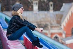 Młoda kobieta siedzi z filiżanki kawą plenerową Obrazy Stock