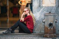 Młoda kobieta siedzi zamyślenie na ulicie w okularach przeciwsłonecznych z blondynek dreadlocks Obrazy Stock