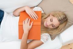 Młoda kobieta spadać uśpiony podczas gdy czytający Zdjęcie Royalty Free