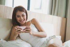 Młoda kobieta sprawdza jej mądrze telefonu lying on the beach w łóżku zdjęcie stock