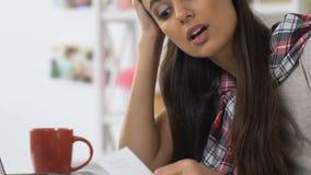 Młoda kobieta sprawdza karta kredytowa koszty dla miesiąca, brak budżet, trwoni zbiory
