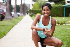 Młoda kobieta sprawdza mądrze zegarków spojrzenia outdoors kamera zdjęcia stock