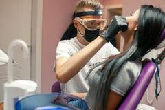 Młoda kobieta sprawdza zęby w stomatologicznym biurze Męski dentysta egzamininuje Fotografia Royalty Free