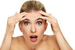 Młoda kobieta sprawdza zmarszczenia na jej czole obraz stock