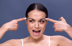 Młoda kobieta sprawdza zmarszczenia na jej czole fotografia stock