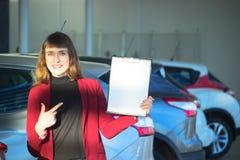 Młoda kobieta sprzedaje samochód zdjęcia stock