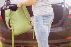 Młoda kobieta stawia bagaż torby w bagażniku samochód zdjęcia stock