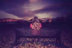 Młoda kobieta stawia czoło daleko od sadzający na ławce fotografia royalty free
