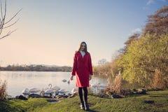 Młoda kobieta stawia czoło w kierunku jeziora z łabędź blisko zdjęcia stock