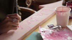 Młoda kobieta stawia listy na drewnianej desce z farbą indoors zbiory wideo