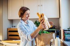 Młoda kobieta stoi indoors w kuchni, odpakowywa torbę na zakupy obrazy stock