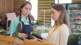 Młoda kobieta stoi w sklepie indoors wybiera świeżych ogórki zdjęcie wideo
