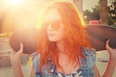 Młoda kobieta stoi w uliczny mienia deskorolka za jej głową _ Uliczny moda styl życia Zdjęcia Royalty Free