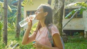 Młoda kobieta stojak na wsi ścieżce w azjatykciej wiosce i wodzie pitnej zdjęcia stock