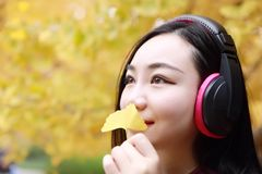 Młoda kobieta stojak pod drzewnym morzem i słuchanie muzyka z hełmofonami zdjęcie royalty free