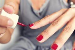 Młoda kobieta stosuje czerwonego gwóźdź poleruje jej paznokcie Fotografia Stock