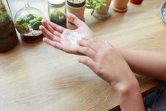 Młoda kobieta stosuje ręki kremowe przy drewnianym stołem Obraz Stock