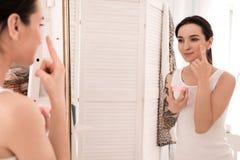 Młoda kobieta stosuje twarzy śmietankę w łazience Ranek rutyna fotografia royalty free