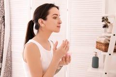 Młoda kobieta stosuje twarzy śmietankę w łazience Ranek rutyna zdjęcie stock