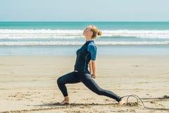 Młoda kobieta surfingowiec rozgrzewkowy w górę plaży na przed surfować obrazy stock