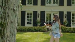 Młoda kobieta szczęśliwie chodzi w parku na zielonej trawie zbiory