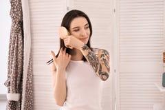 Młoda kobieta szczotkuje jej włosy w domu Ranek rutyna fotografia stock