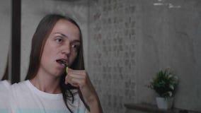 Młoda kobieta szczotkuje jej zęby z toothbrush w łazience zbiory