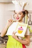 Młoda kobieta szef kuchni patrzeje przepis książkę w kuchni Zdjęcie Stock