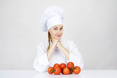 Młoda kobieta szef kuchni pokazuje pomidory dla włoskiego jedzenia na bielu Obrazy Stock