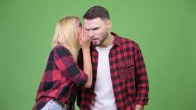 Młoda kobieta szepcze młody człowiek i patrzeje nierady zbiory wideo