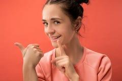 Młoda kobieta szepcze sekret za ona oddaje koralowego tło fotografia royalty free