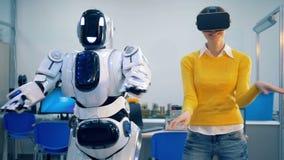 Młoda kobieta tancząca i cyborg ruszamy się ich biodra w synch i ręki podczas gdy zbiory wideo