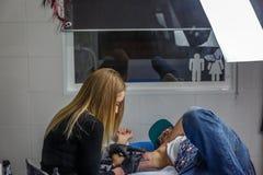 Młoda kobieta tatuuje prawe ramię mężczyzna w jej studiu, obraz stock