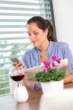 Młoda kobieta texting czytelniczego gazetowego telefon komórkowy Obrazy Stock