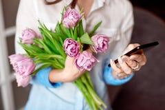 Młoda kobieta texting na jej smartphone z spojrzeniem koncentracja gdy stoi przeciw błękitnej ścianie obraz stock